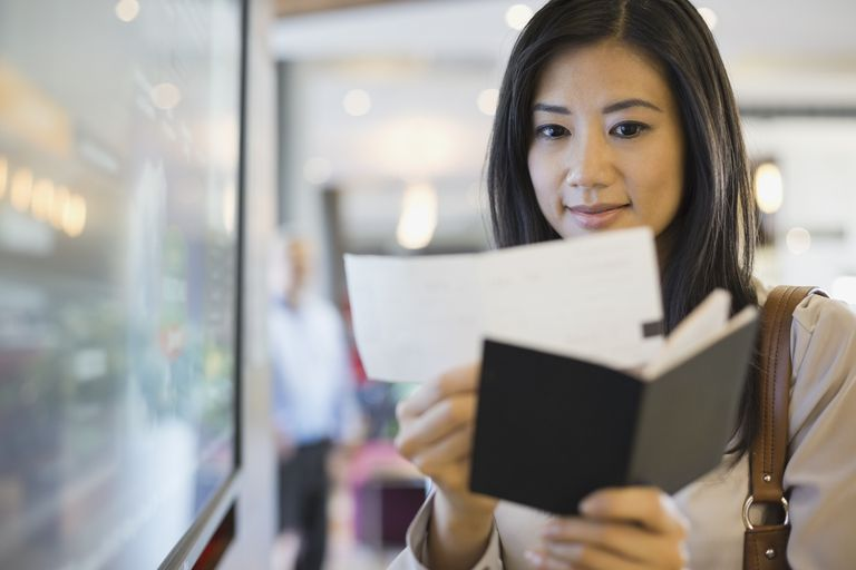 Businesswoman holding up boarding pass and passport
