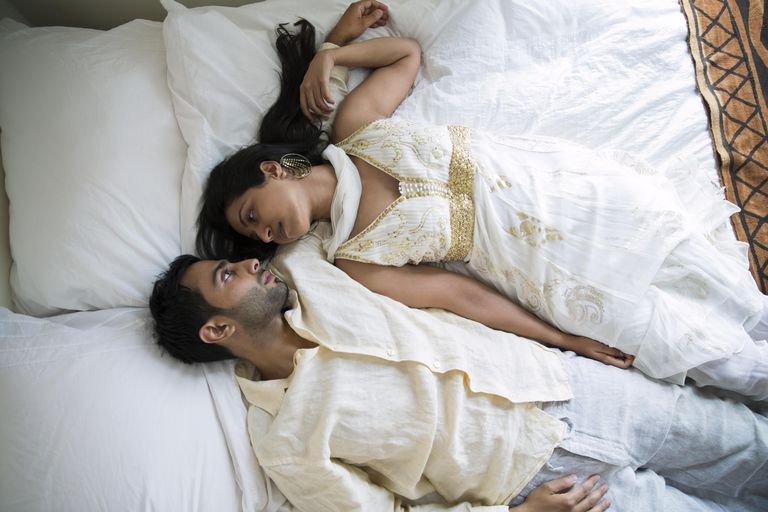 Indian Laying Together On A Bed