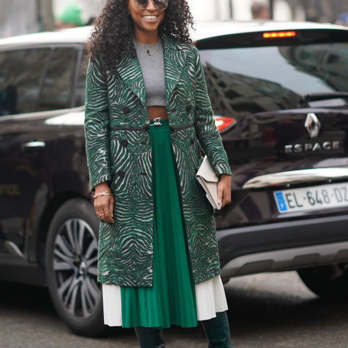 Street style woman in green pleated skirt and patterned coat