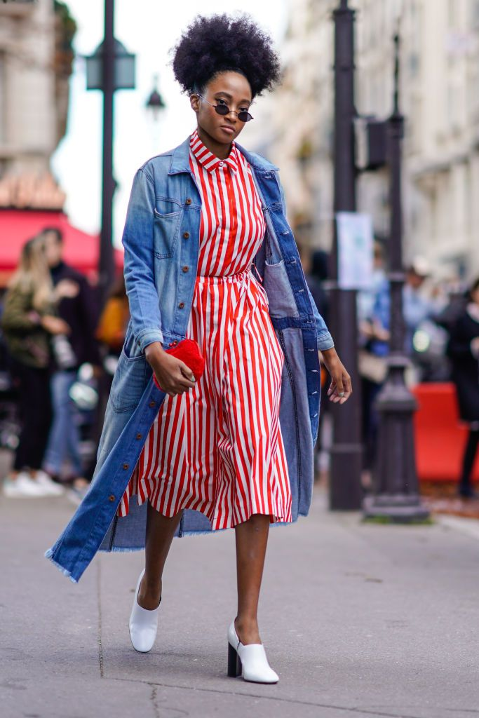 Woman wearing striped dress and denim coat and white ankle boots