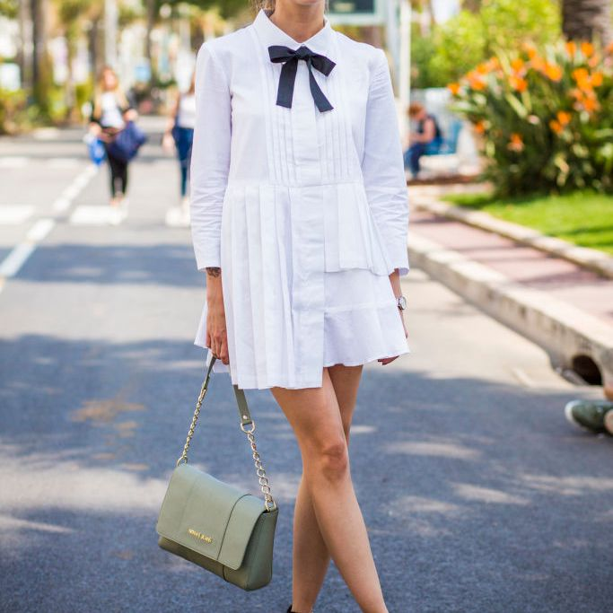 Woman wearing little white summer dress with black bow
