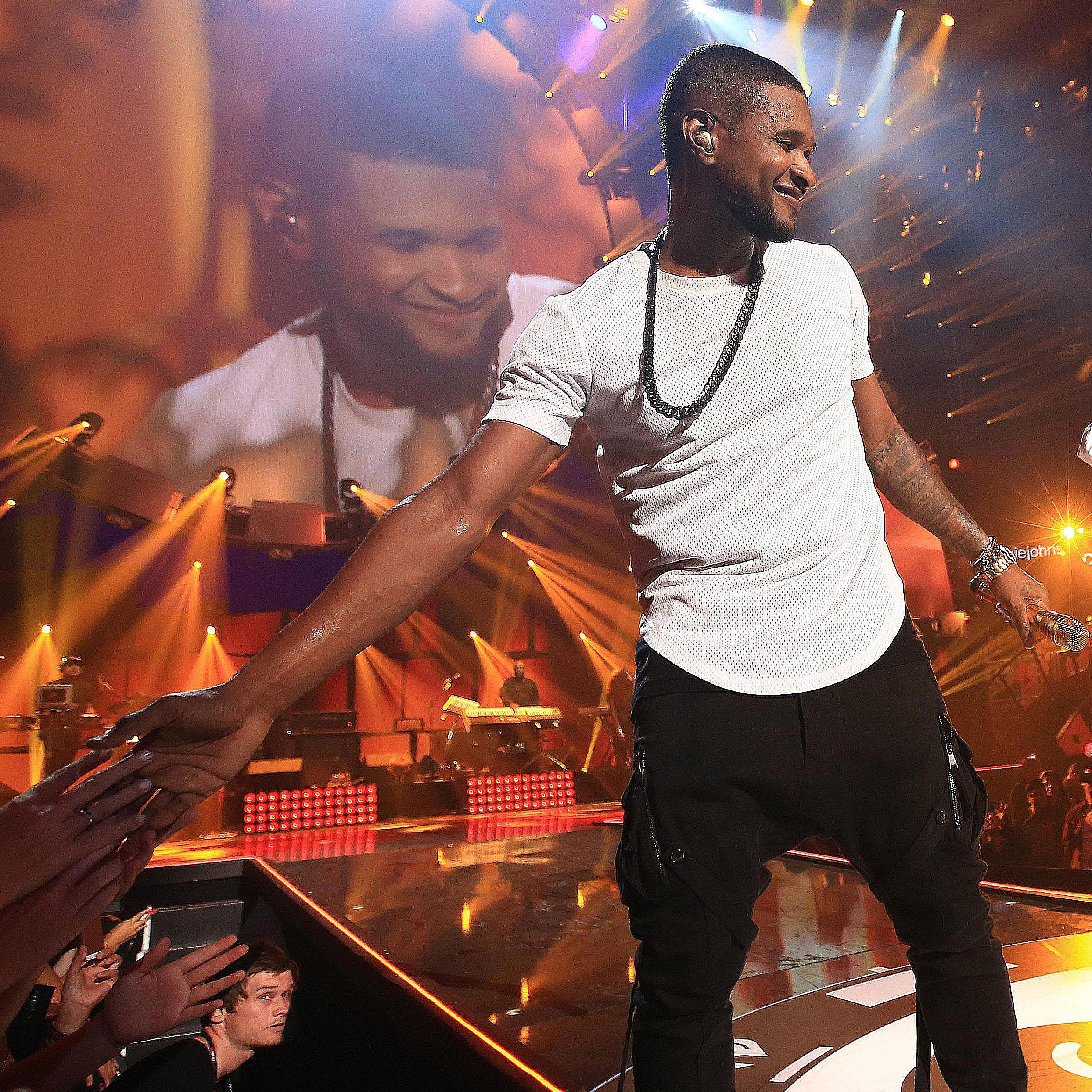 Usher high-fives fans during a performance