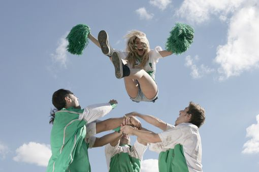 Football players throwing cheerleader in air
