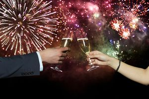 Couple toasting with champagne, New Year celebration fireworks in background
