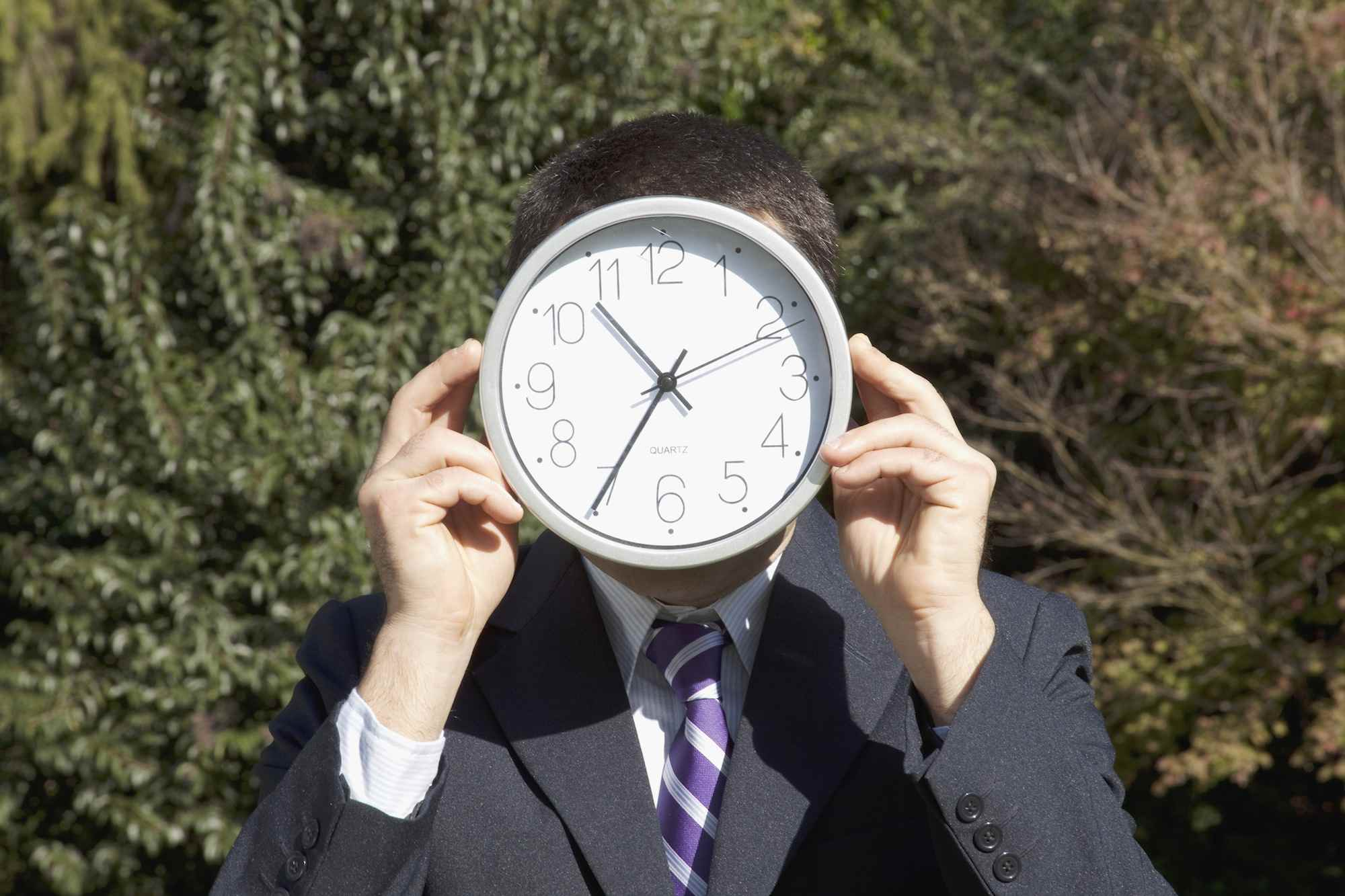 Businessman holding a clock in front his face