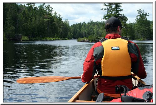 A canoeist sports his pfd, paddle, paddling jacket, and canoe as he enjoys the moment's serenity.