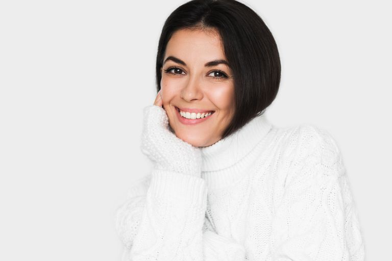 Brunette woman wearing a white turtleneck sweater