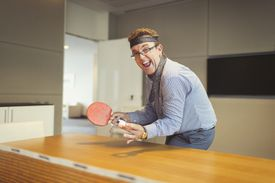 A guy holding a ping pong ball and paddle with his tie wrapped around his head