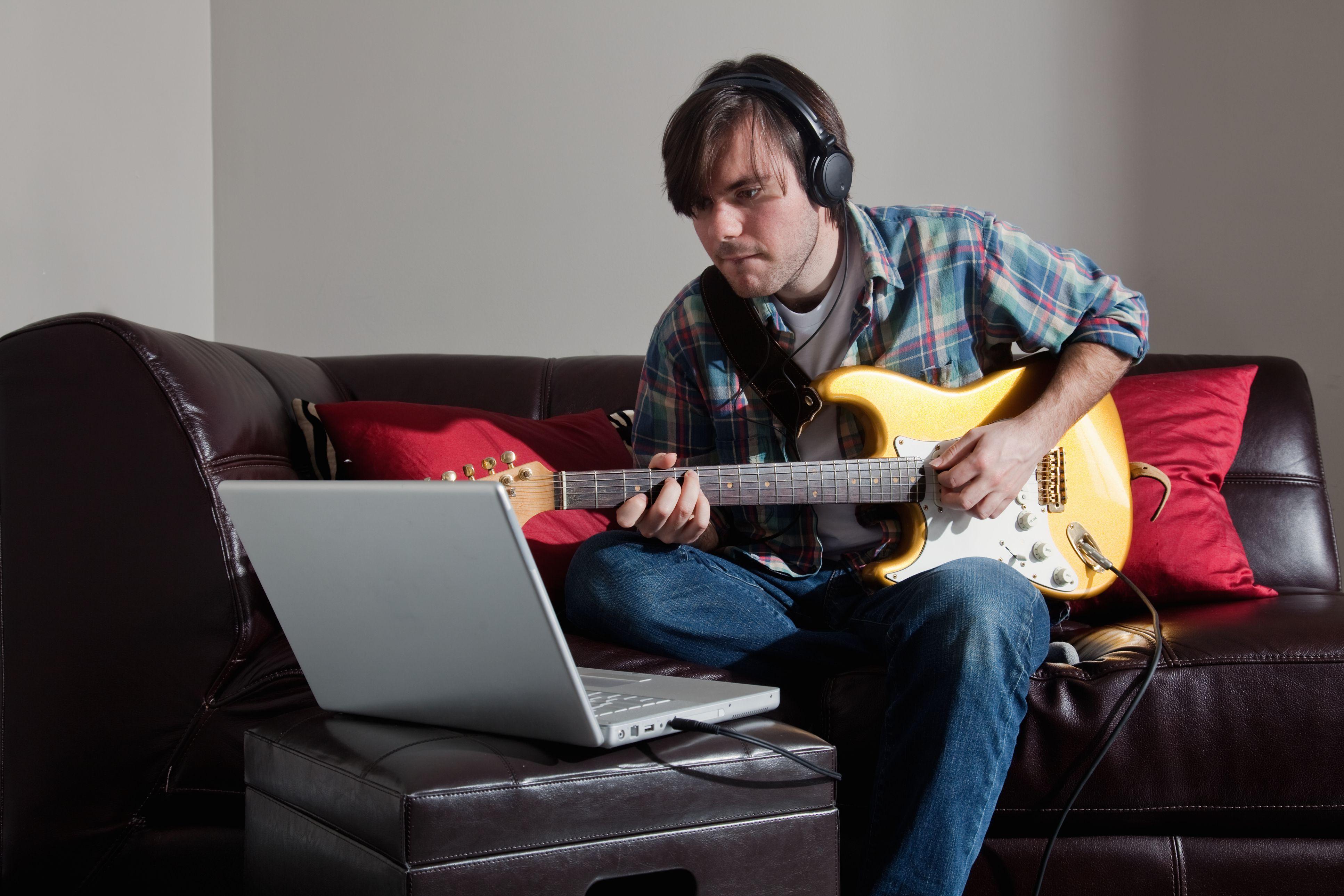 Man playing guitar wile looking at laptop