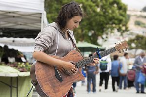 A young woman playing a guitar at a farmer's market in an urban setting.