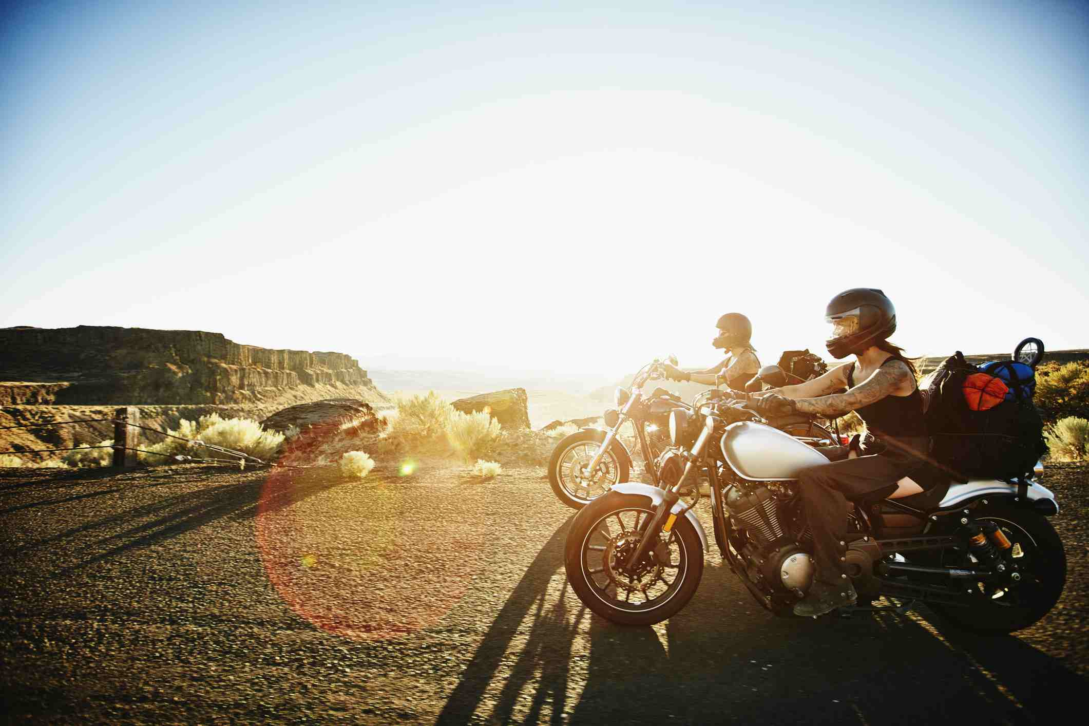 Female motorcyclists riding on desert canyon road on summer evening