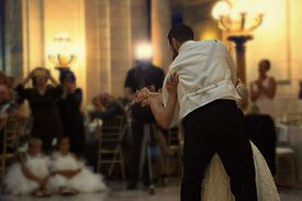 Couple dancing at a wedding with guests looking on.