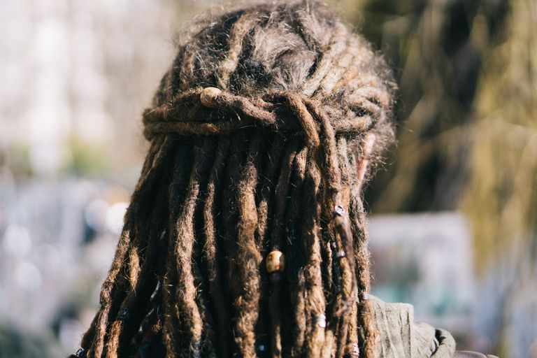Person with dreadlocks facing away from the camera