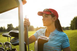 Women golfer retrieves a club from her golf bag.