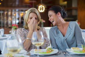 two mature female friends laughing at a restaurant
