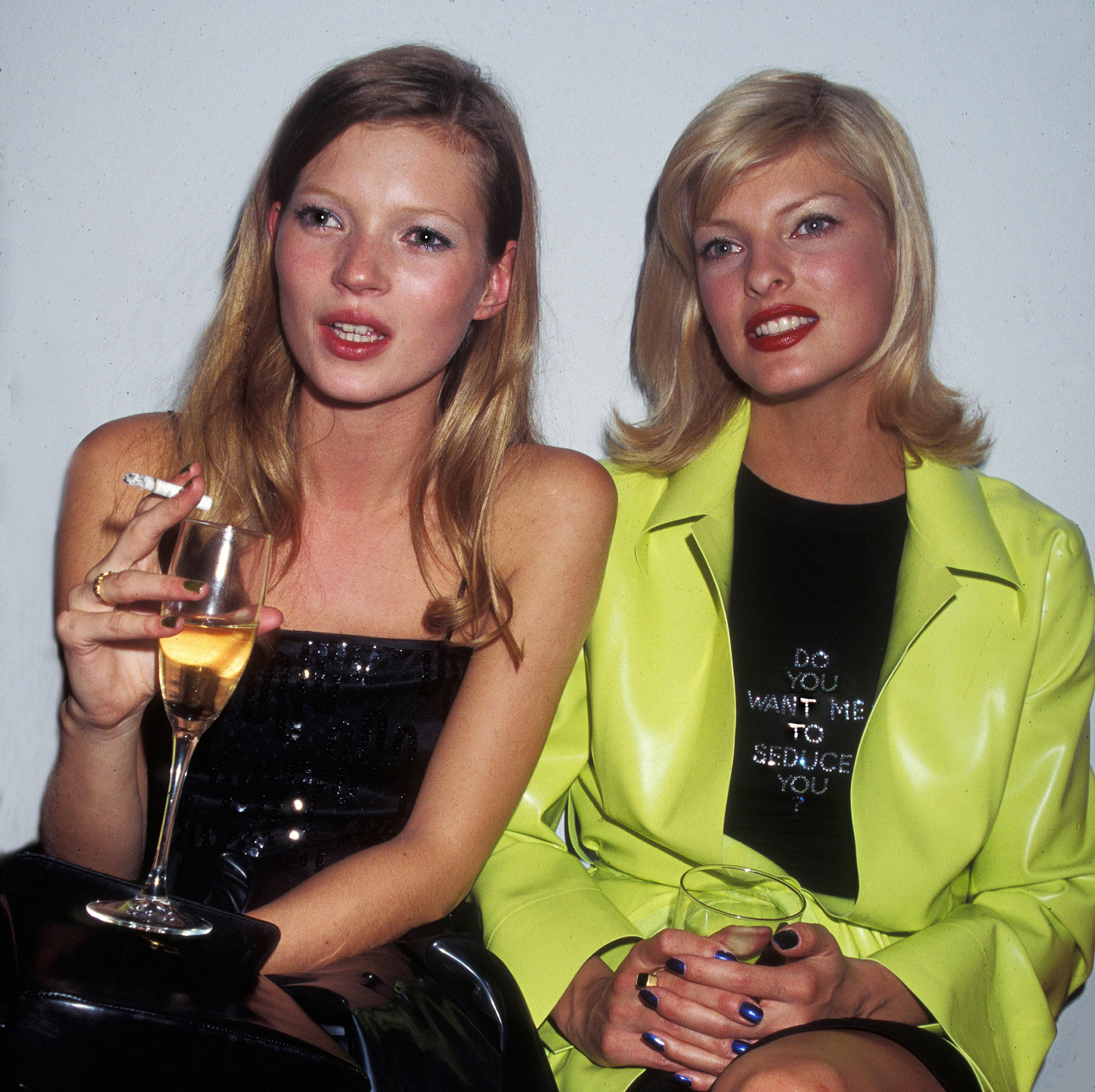 Models Kate Moss and Linda Evangelista attend an Allure Magazine party in a Soho loft, New York, New York, 1994.