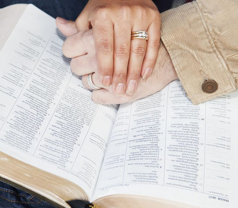 Couples Hands On Top Of A Bible