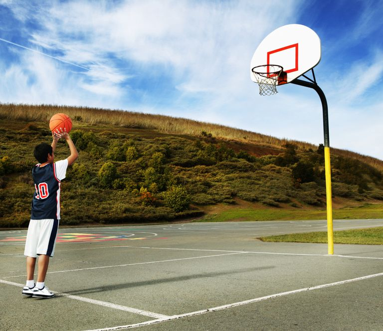 Boy (9-1) preparing to shoot basketball, rear view