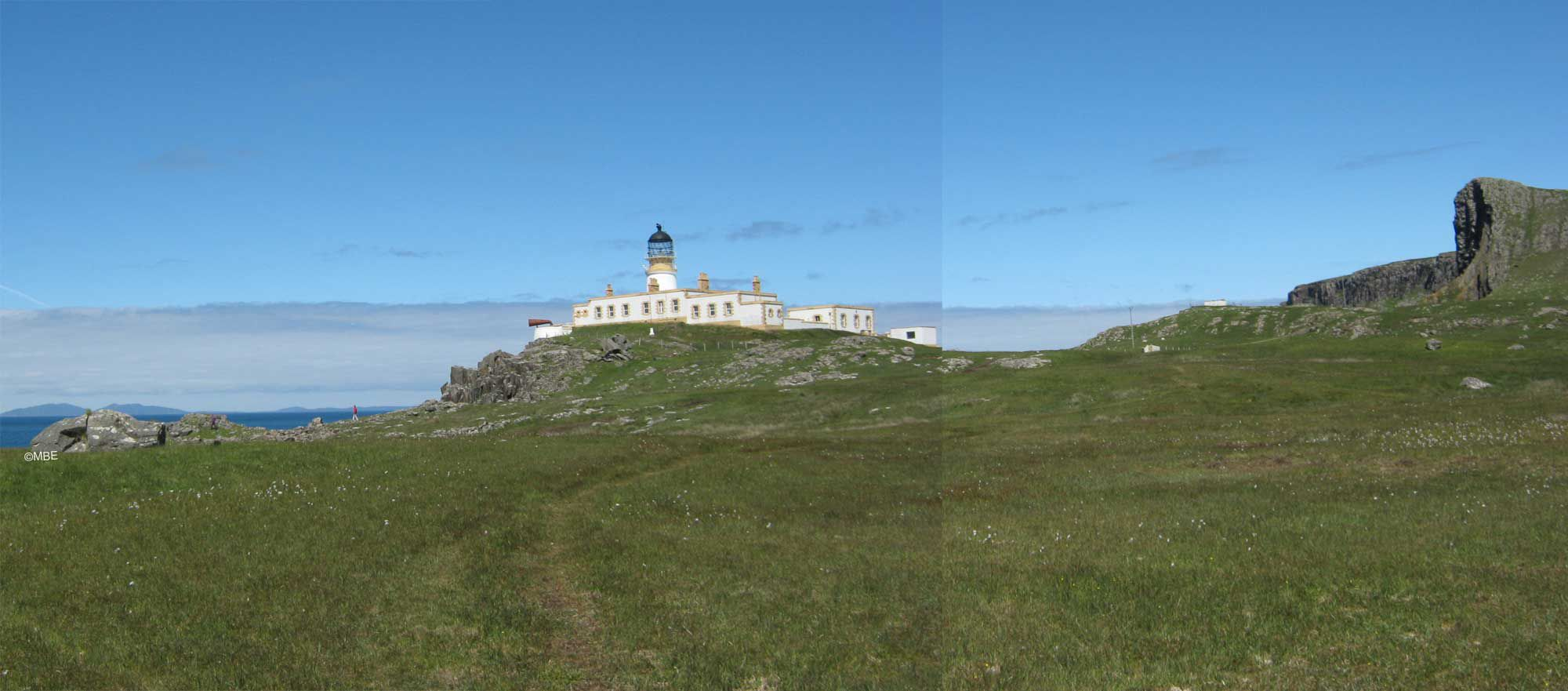 Neist Point Lighthouse, Isle of Skye, landscape photograph taken on a sunny day with a blue sky.
