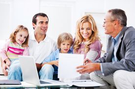 A young couple with children talking to financial advisor.