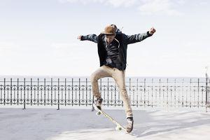 Germany, Schleswig Holstein, Teenage boy jumping with skateboard