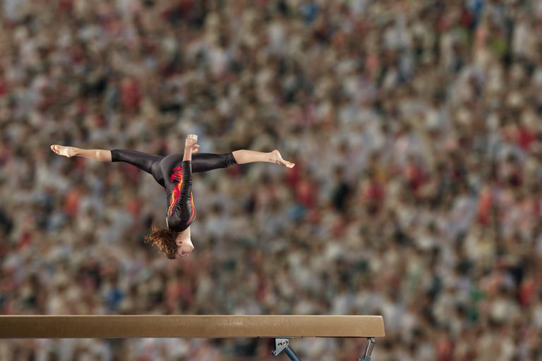 Hispanic gymnast in mid-air over balance beam