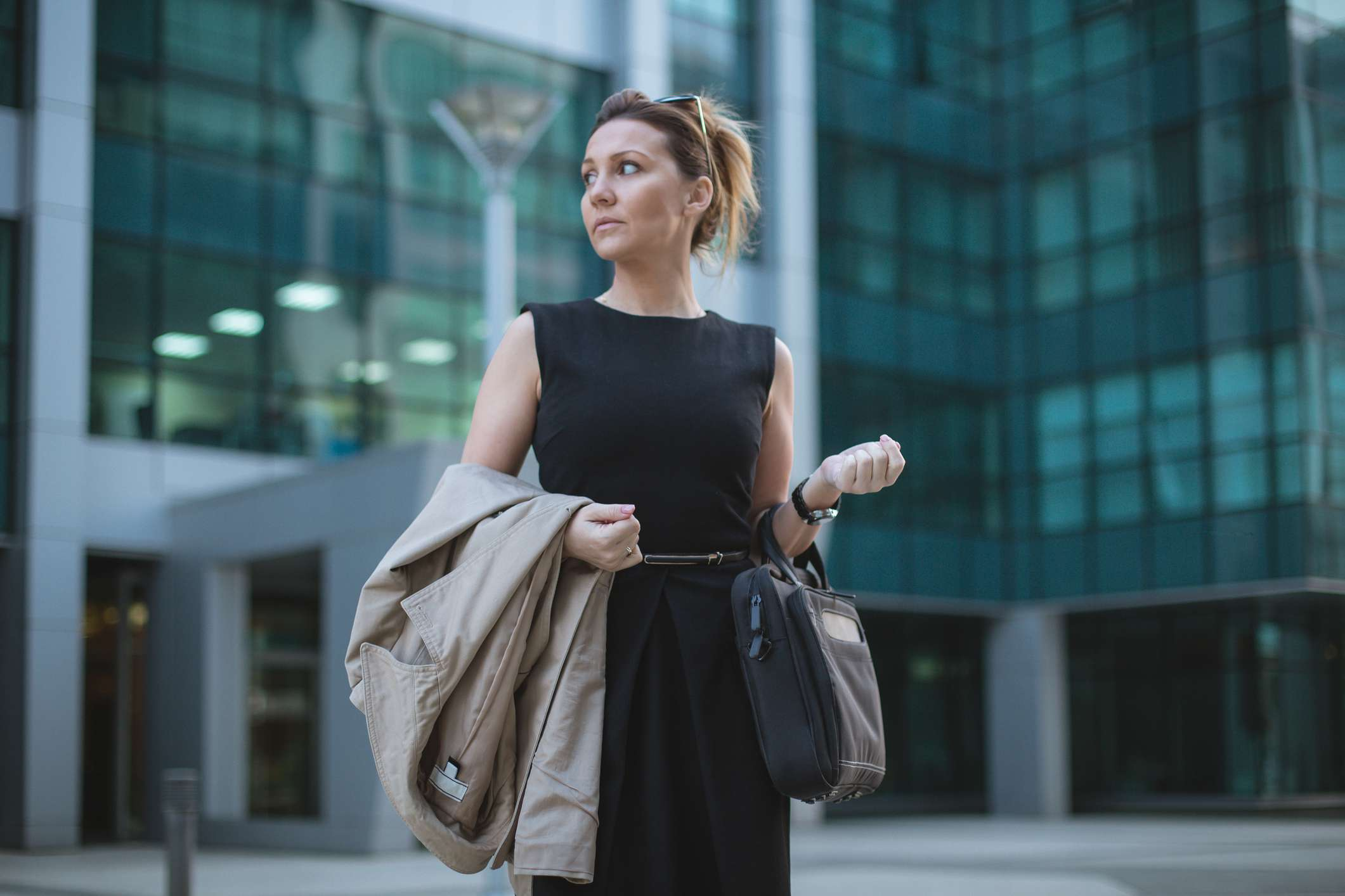 Women in Black Dress Waiting in front of a business building
