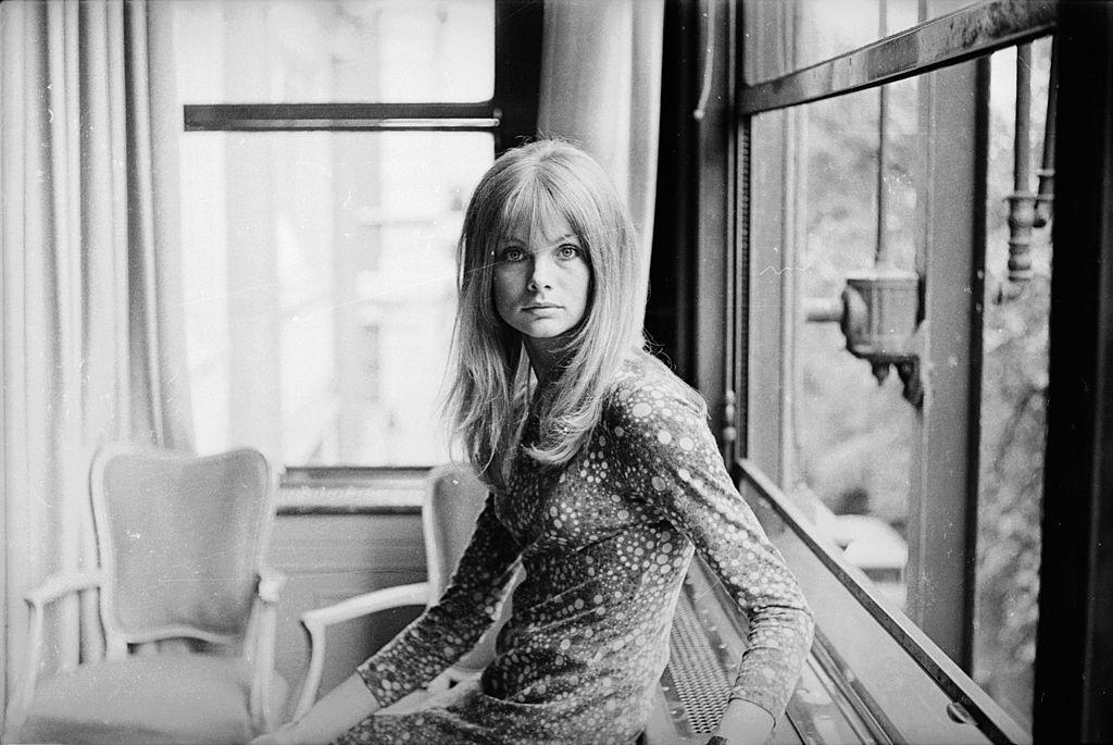 Model Jean Shrimpton sitting next to a window.