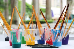 Different paint colors in cups with art brushes sticking out.