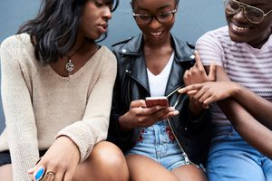 Three friends sitting side by side looking at cell phone