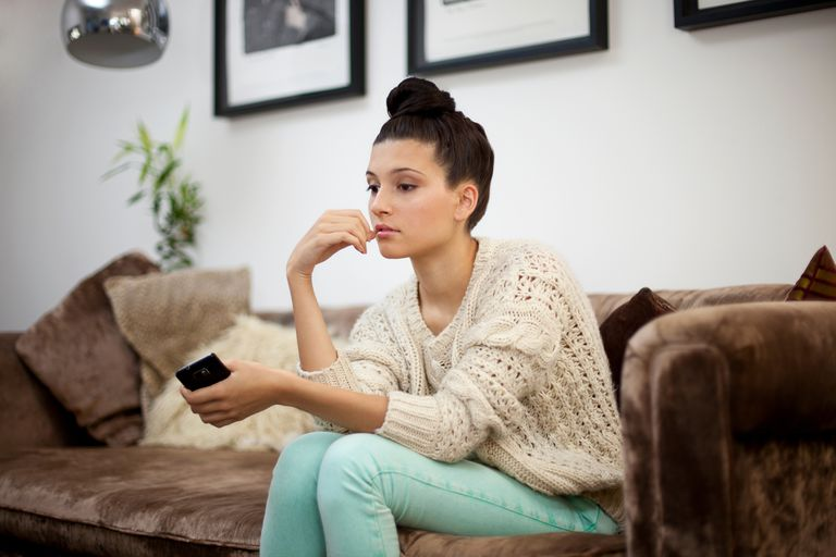 Young woman sitting on sofa with smartphone