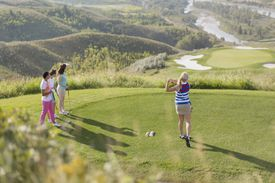 A golfer tees off while her teammates watch.