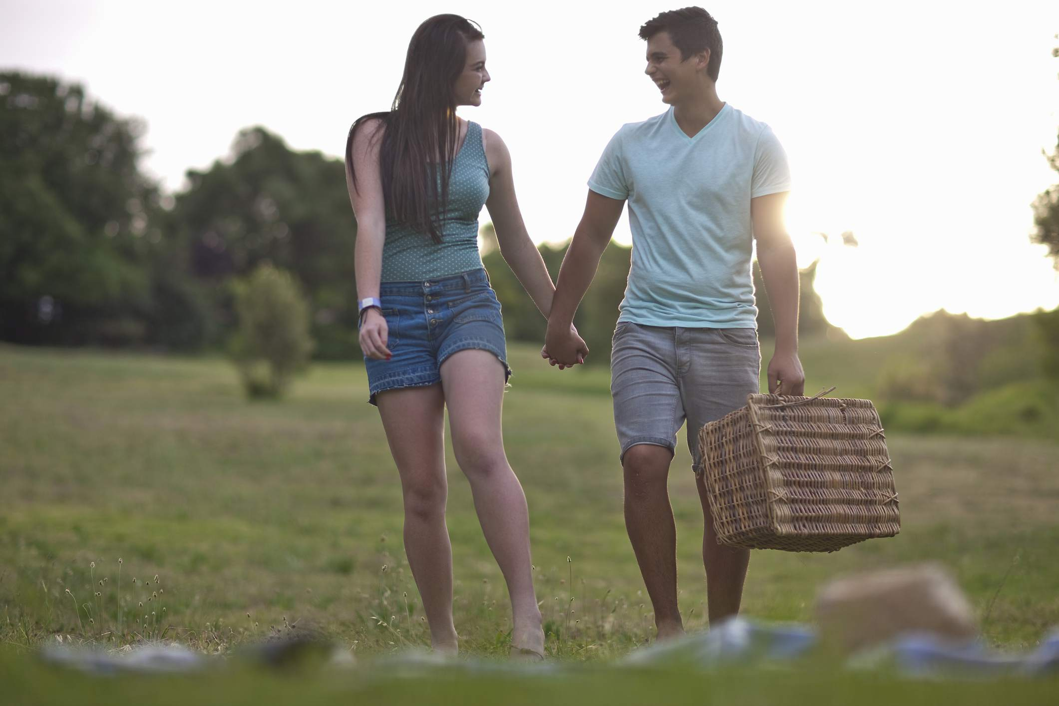 Teenage couple going for picnic in forest