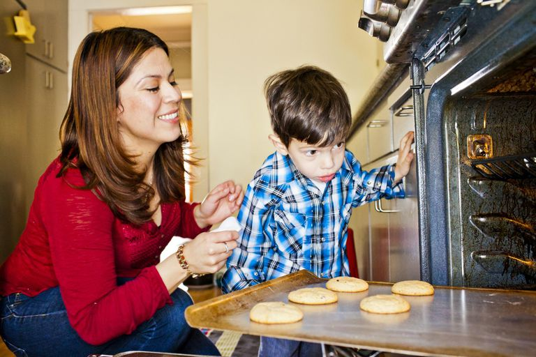 A mother and son baking inside of a kitchen.
