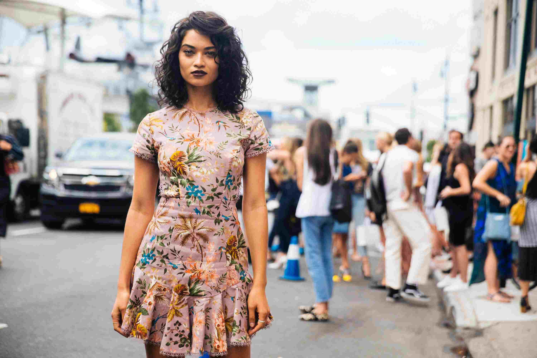 Shanina Shaik wearing a floral dress on a city street.