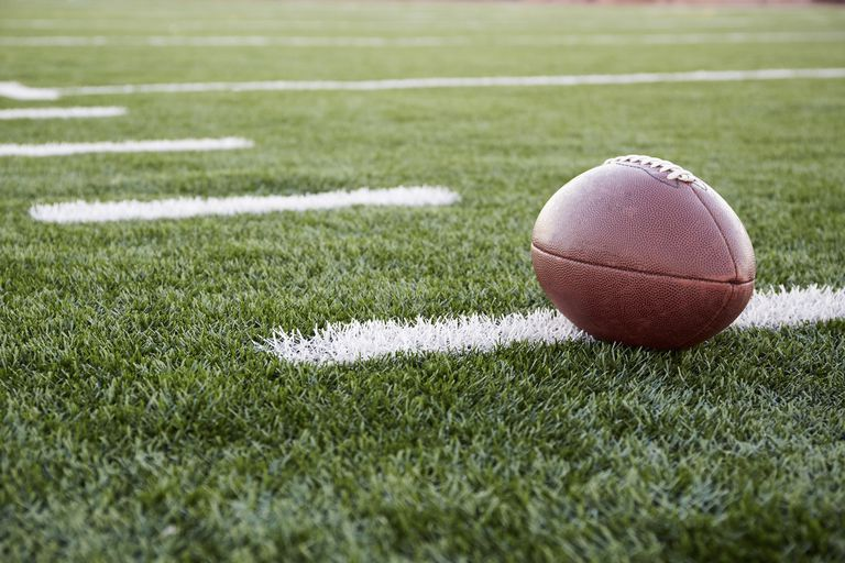 Close up of American football ball on green playing field