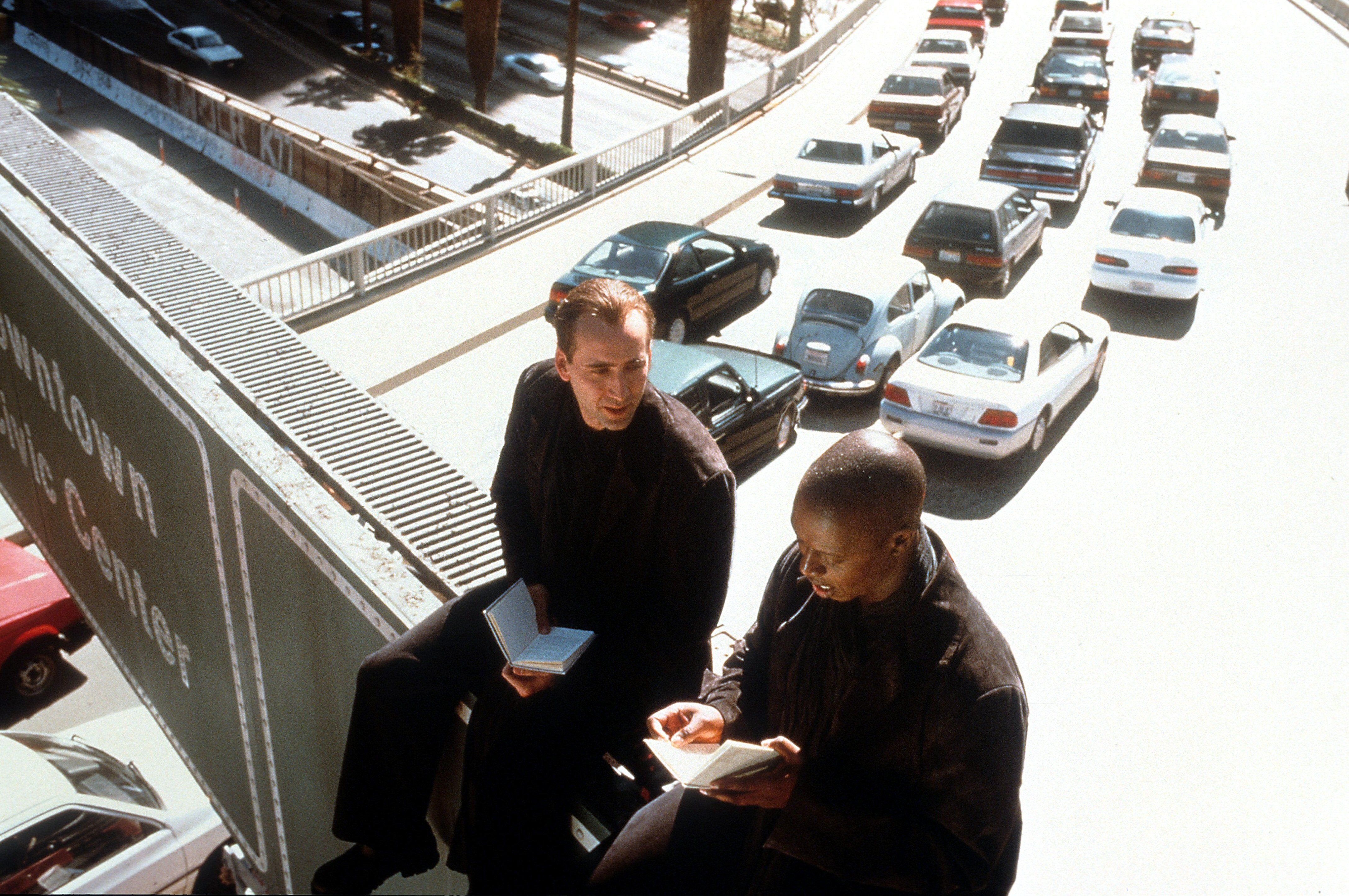 Nicolas Cage and Andre Braugher are sitting on a freeway overpass sign with heavy traffic below them in a scene from the film 'City Of Angels', 1998