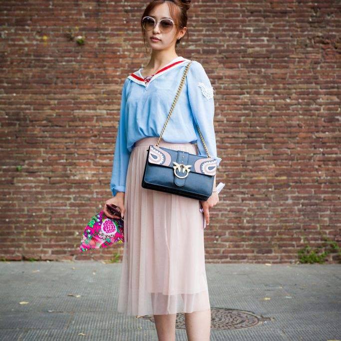 Woman wearing blue blouse and pink pleated skirt