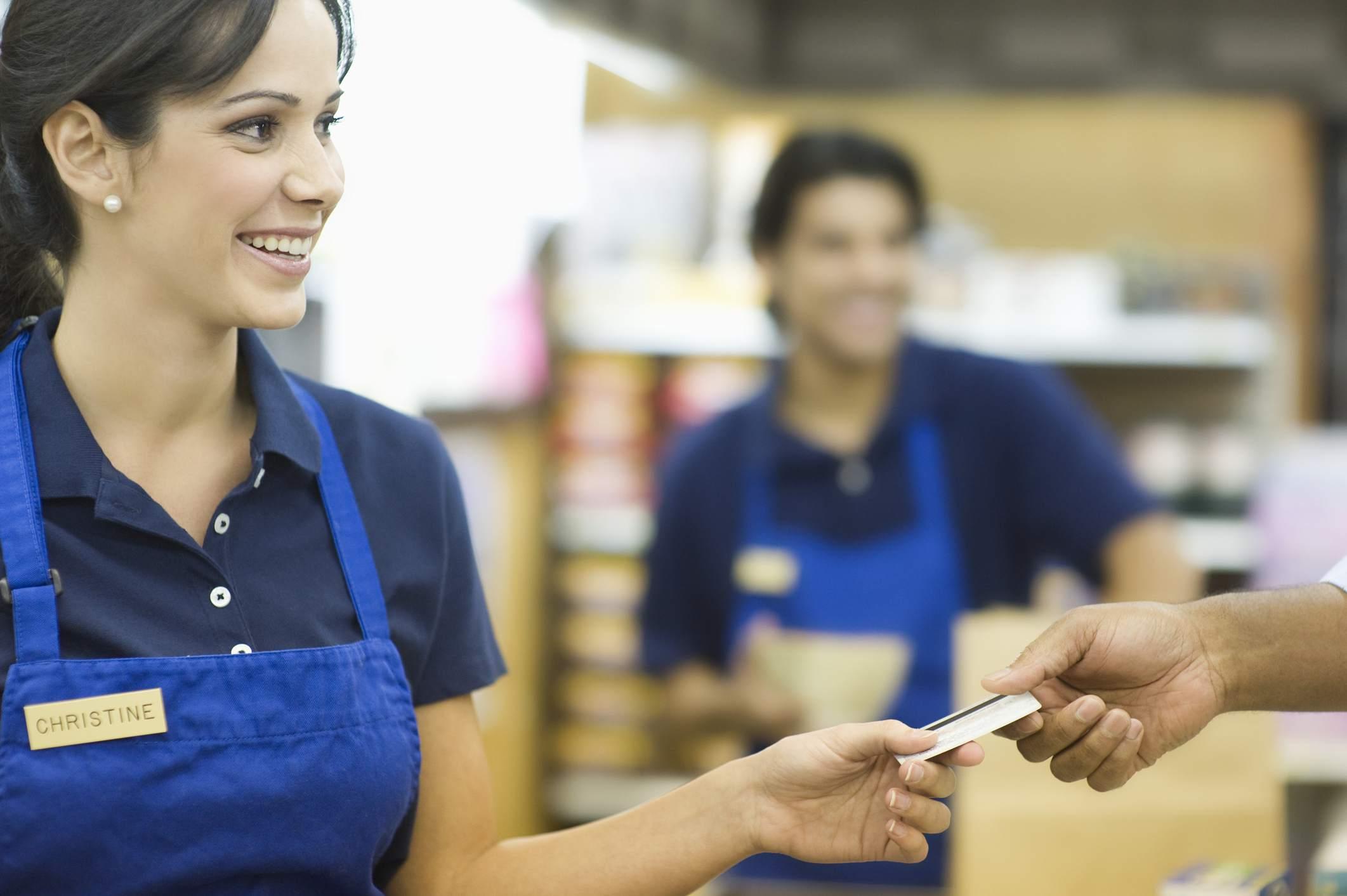 Customer handing cashier store loyalty card