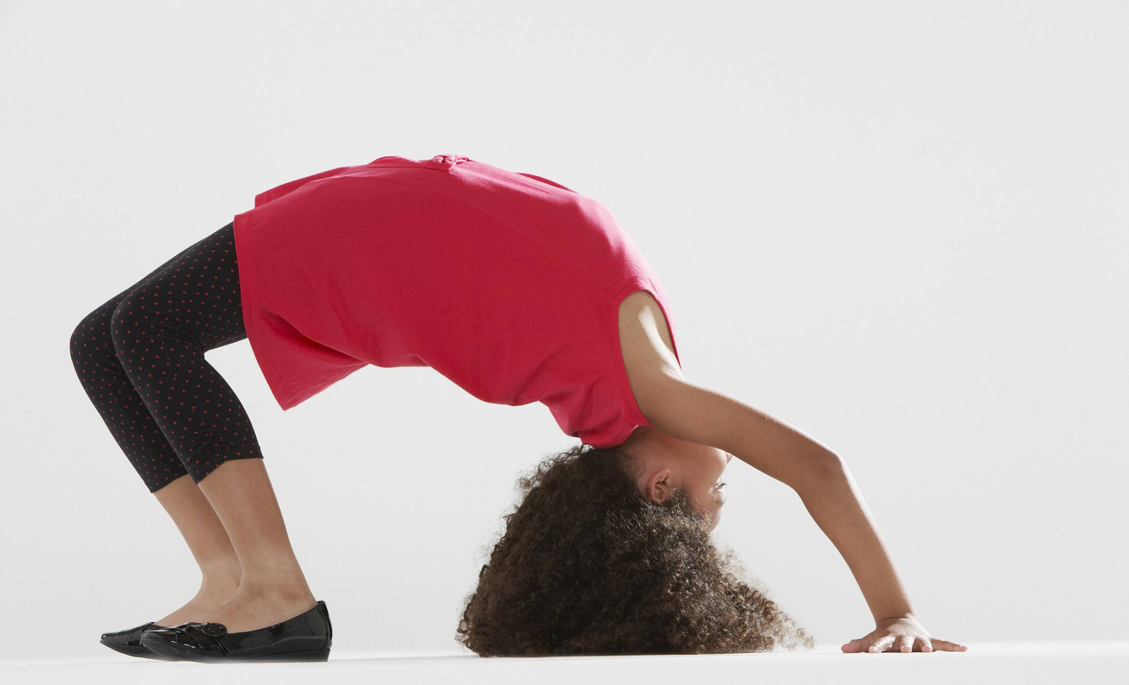Young girl indoors doing back walkover