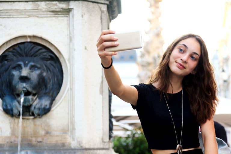 A teenager snaps a selfie beside a lion-shaped fountain