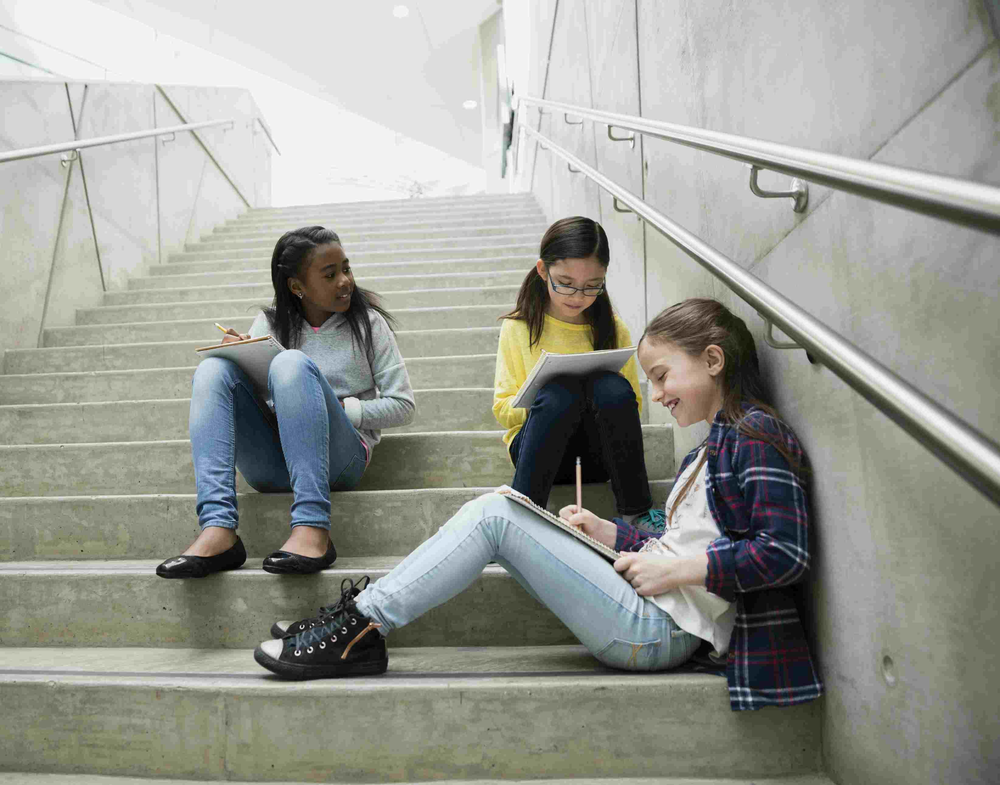 Schoolgirls doing homework on stairs outside