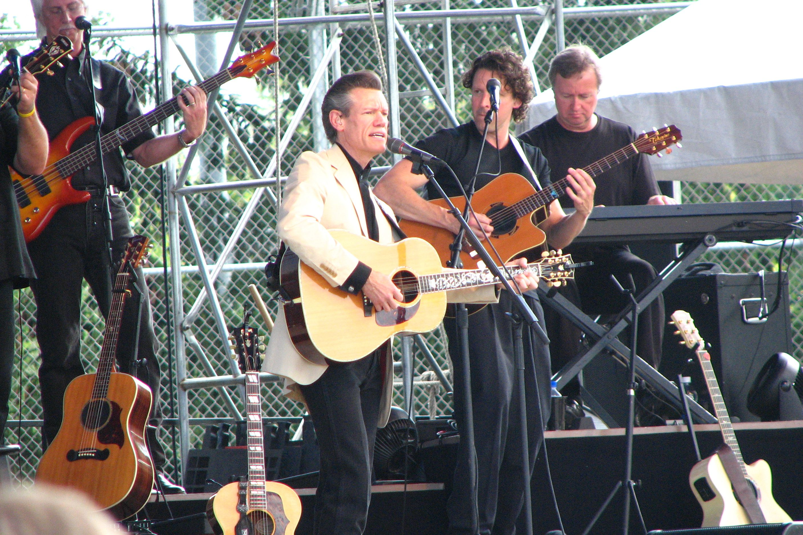 Randy Travis performs on an outdoor stage.