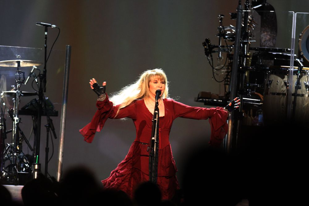 Stevie Nicks at the microphone performing on stage.