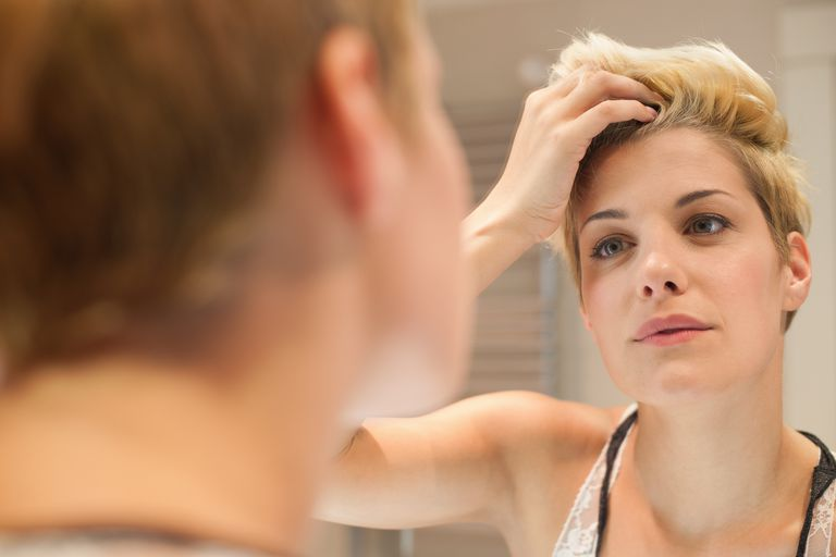 woman with short hair looking in mirror