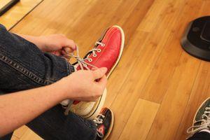 a person tying a bowling shoe