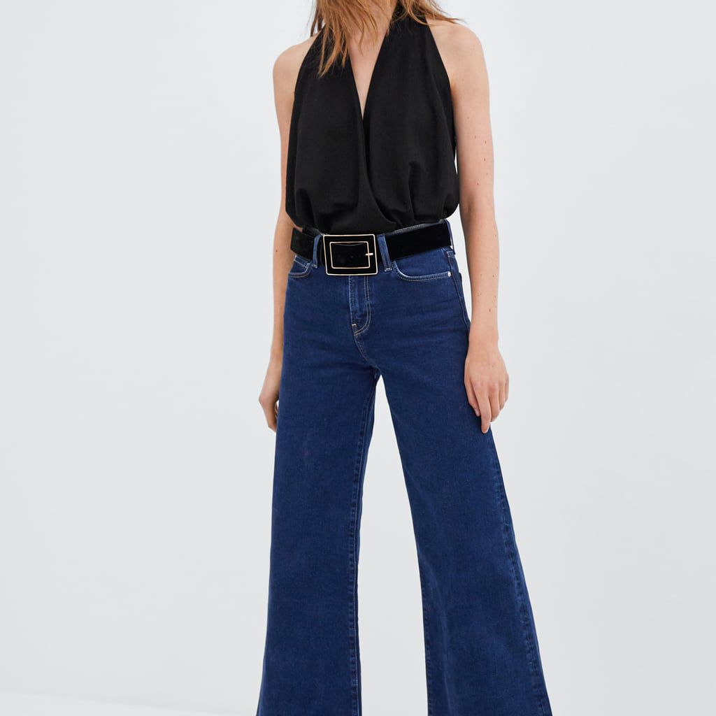 Woman in black v-neck top and flare jeans