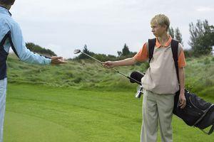 male teenage caddy giving golf club to man