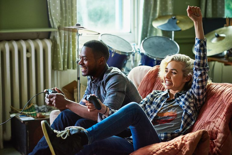 Man and woman with controllers playing PS3 game on couch