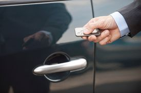 Man's hand holding a remote next to closed car door